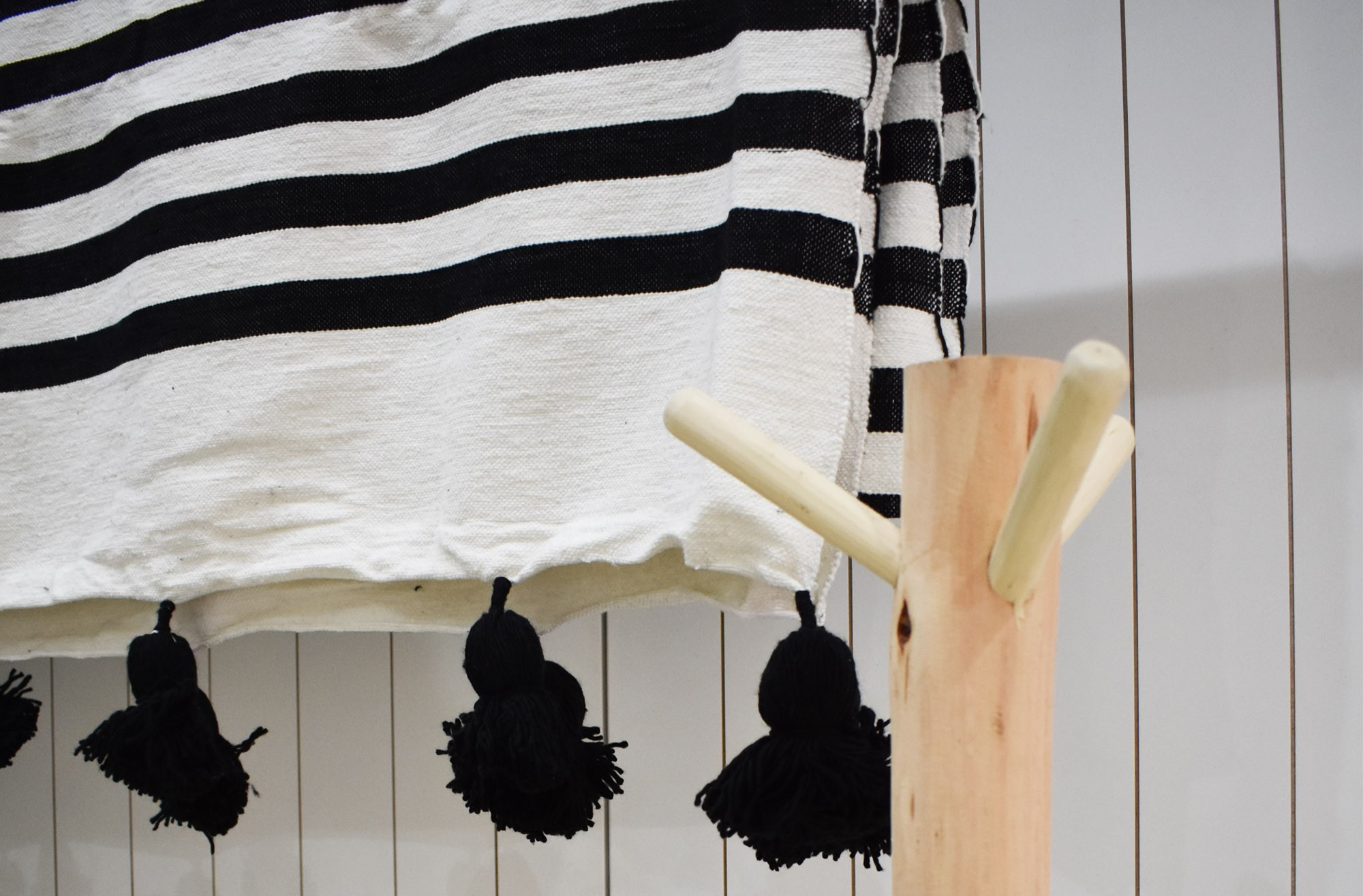 Black and white striped blanket with white wool pompoms