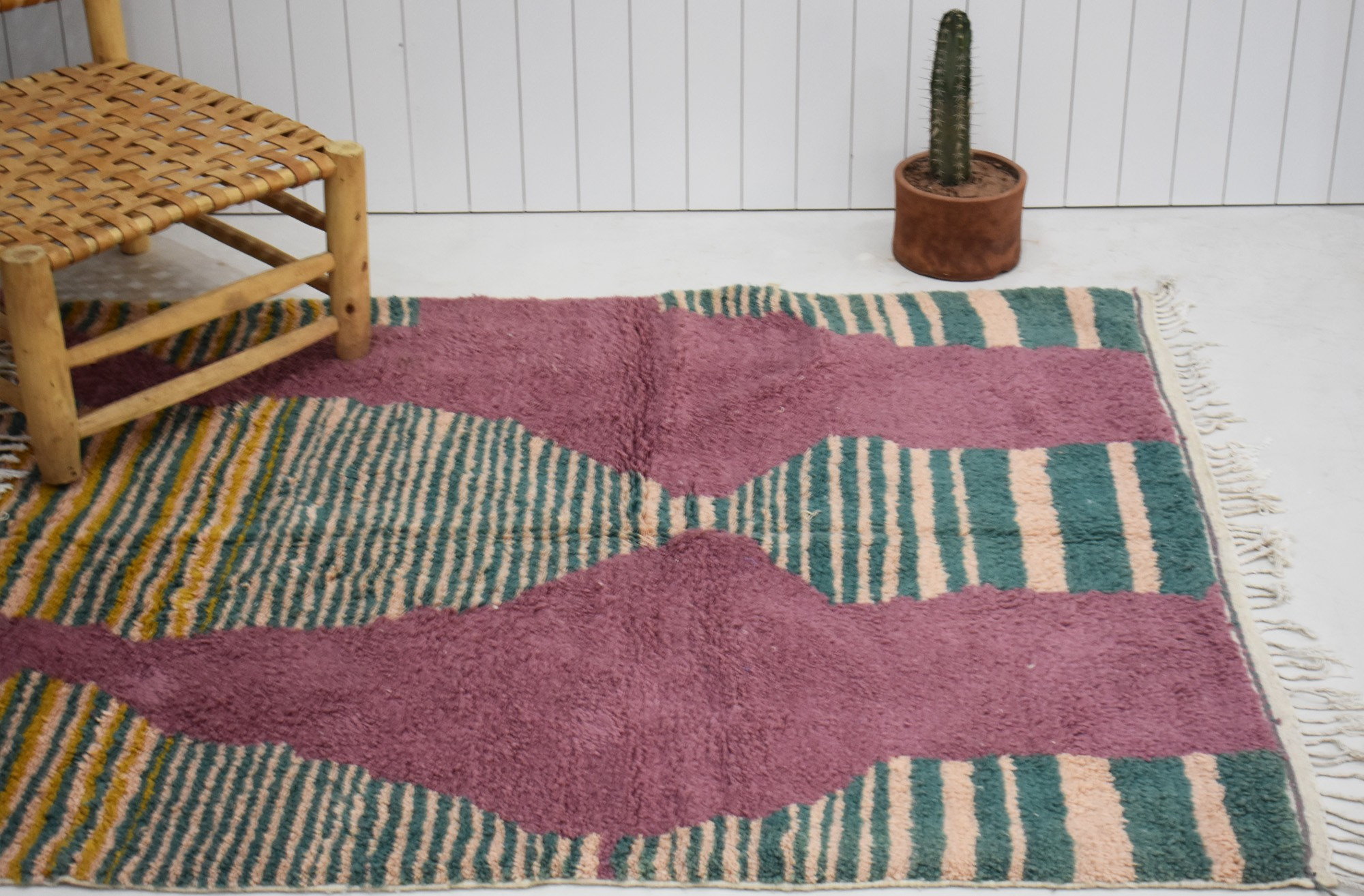 Pink background rug and silhouette patterns in green, yellow and pale pink