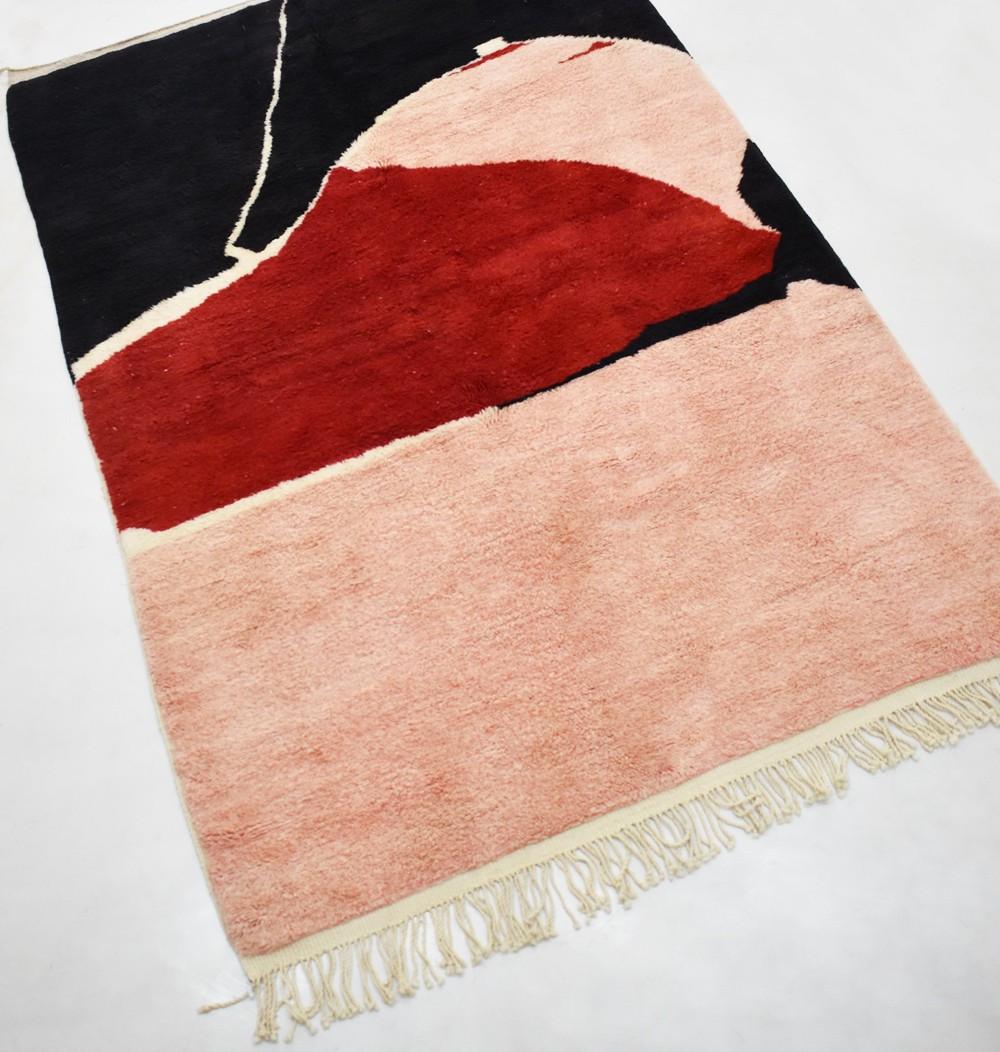 Tapis berbère aux tons de noir, brique, rose et beige