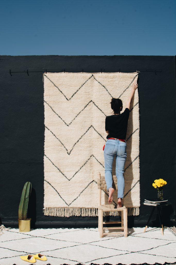 Tapis beni ouarain noir et blanc et femme berbere avec cactus